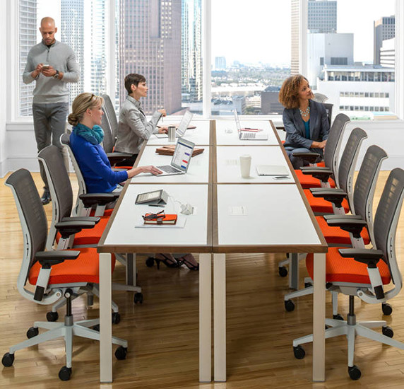 Modern boardroom interior design featuring long bench table, whiteboard and orange Steelcase task chairs