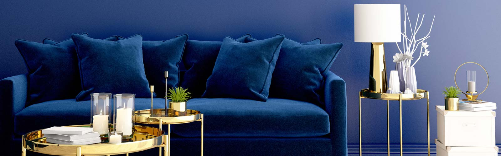 Blue velvet sofa behind gold coffee tables against blue wall in Pantone Color of the Year Classic Blue